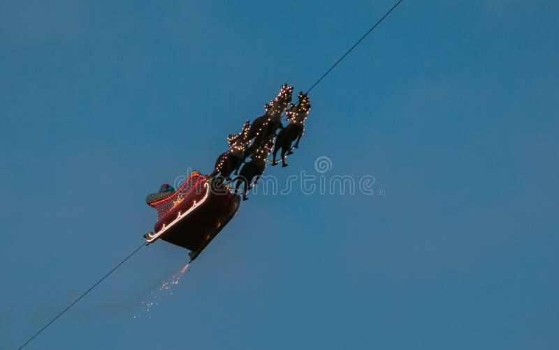 Släden av Santa Claus med renflyg i himlen på skymning, Montreux, Schweiz royaltyfri bild