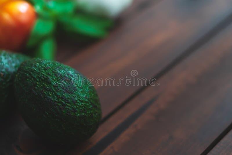Släktklenodtomater och avokado på ett brunt bräde fotografering för bildbyråer