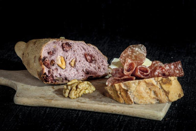 Släntra av fransk sourdough, kallat också smärtar de campagne som stoppas med kött och valnötter på en svart bakgrund med en skiv arkivfoton
