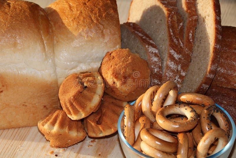 Släntra och skivor av nytt bröd på en solig tabell arkivbilder