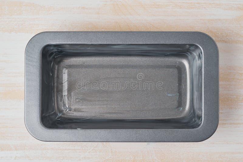 Släntrar den inoljade stekheta maträtten för olja, bröd pannan med smör E arkivfoton