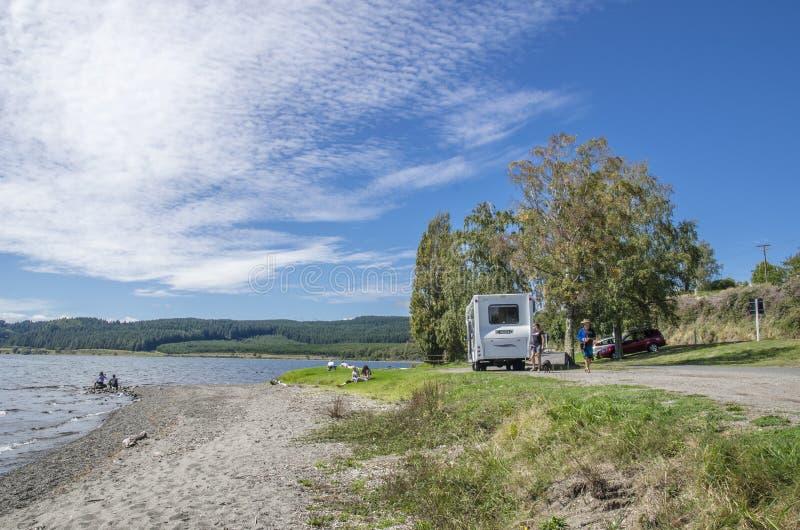 Släphusvagn i sjön Taupo, Nya Zeeland Folket kan sedd undersökning runt om den arkivbilder