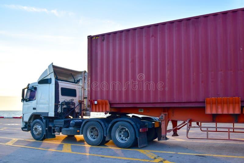 Släplastbil som laddas med fyrtio fot behållare under kajkranen arkivfoto