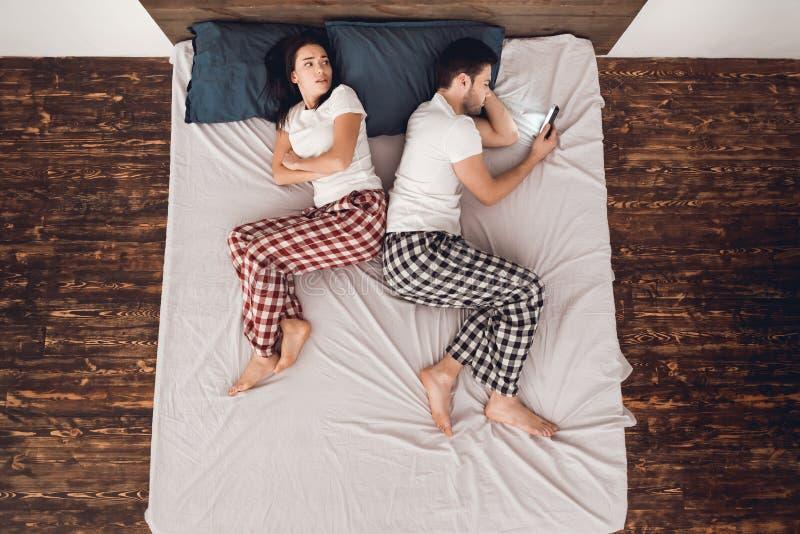 Släpsikt Den vuxna stiliga mannen med telefonen i händer förhindrar att sova bredvid liggande ung kvinna royaltyfri fotografi