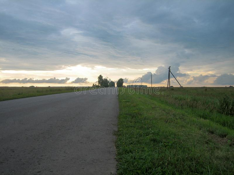 Slät rak asfaltväg i bygden under himlen med moln på solnedgången royaltyfria bilder