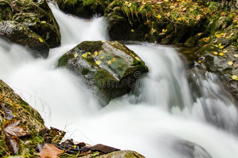 Slät vattenyttersida av vattenfallet i hösten, lång exponeringseffekt royaltyfri fotografi