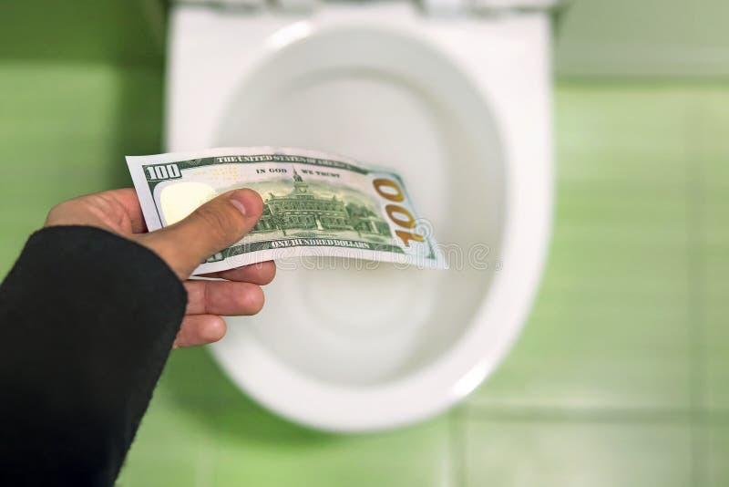 Släta pengar ner toaletten, kastdollarräkningar i toaletten, förlustbegrepp, slut upp, selektiv fokus royaltyfri bild