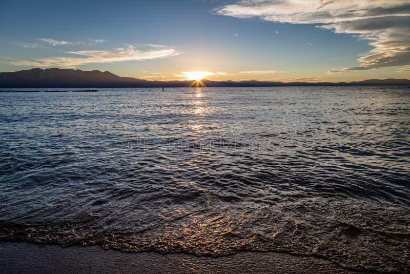 Slätt vatten reflekterar med den guld- solinställningen bak plana berg i avståndet som ser från Lakesidestranden på sjön arkivfoton