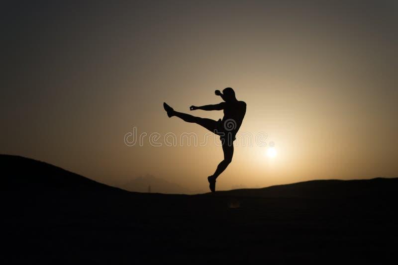 Slå ditt mål Hopp för konturmanrörelse framme av solnedgånghimmelbakgrund Daglig motivation Sund livsstil arkivfoto