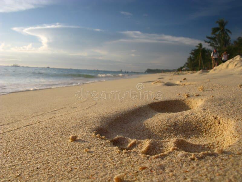 slå för sand för strandfottryck som är tropiskt arkivfoto