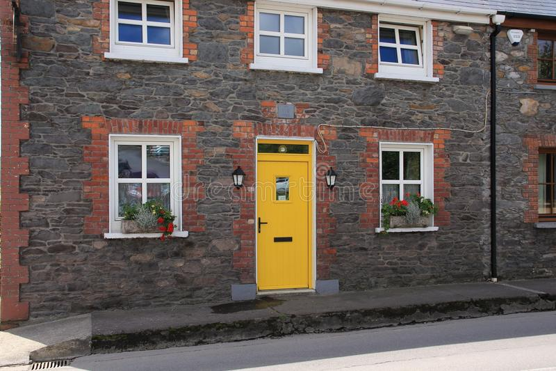 Slående gul dörr av i bydinglen i ståndsmässiga Kerry i Irland i sommaren arkivfoto