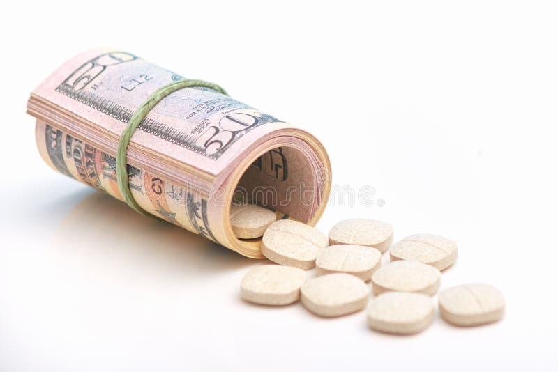 Slågna in dollar och medicinpreventivpillerar över vit bakgrund Betald medicin- och korruptionbegrepp Dollarsedel Olaglig medicin arkivbild