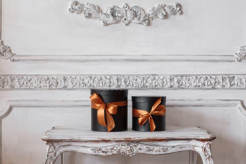 Slågna in svarta askar för gåva med band, som julklappar på en lyxig vit vägg för tabell planlägger basreliefstuckaturen royaltyfri bild