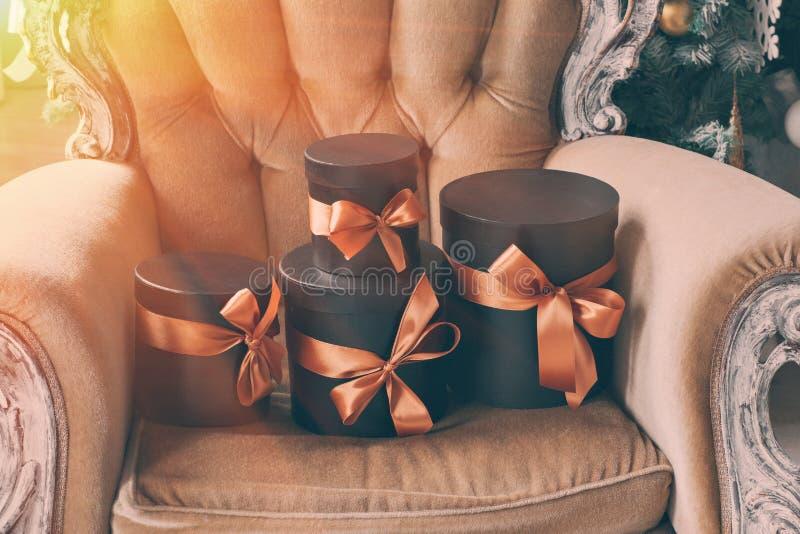 Slågna in svarta askar för gåva med band som julklappar på en stol royaltyfria foton
