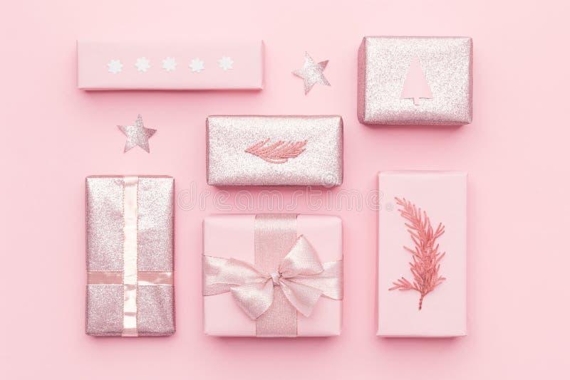 Slågna in xmas-askar Rött boxas med pilbågen Rosa nordiska julgåvor som isoleras på bakgrund för pastellfärgade rosa färger royaltyfria foton