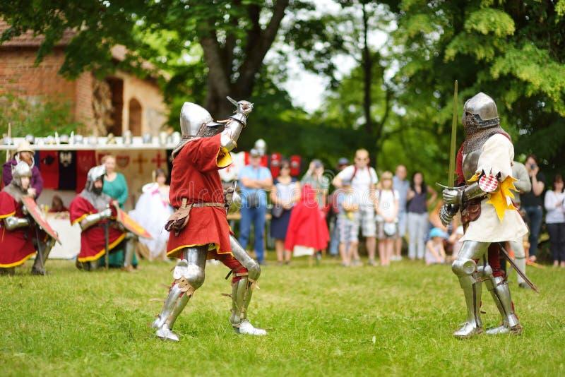 Slåss bärande riddaredräkter för folk under historisk reenactment på den årliga medeltida festivalen som rymms i Trakai den halvö royaltyfri fotografi