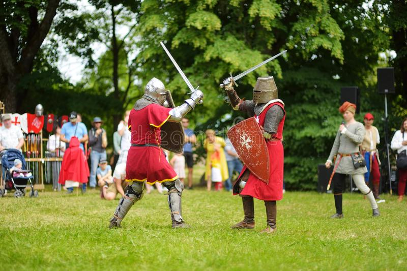 Slåss bärande riddaredräkter för folk under historisk reenactment på den årliga medeltida festivalen som rymms i Trakai den halvö fotografering för bildbyråer