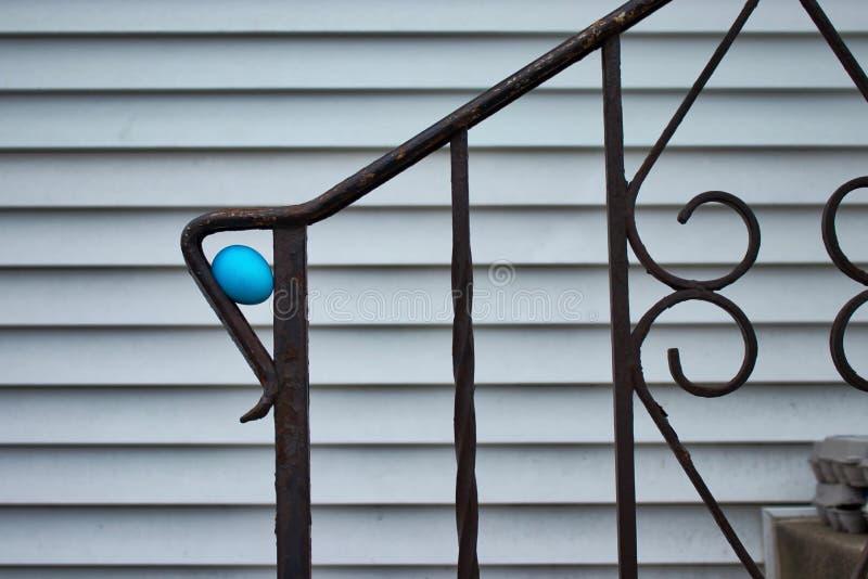 Slösa det färgade påskägget som döljas för en äggjakt, i skurk av staketräcket på konkret trappa av det mellanvästern- hemmet royaltyfri bild