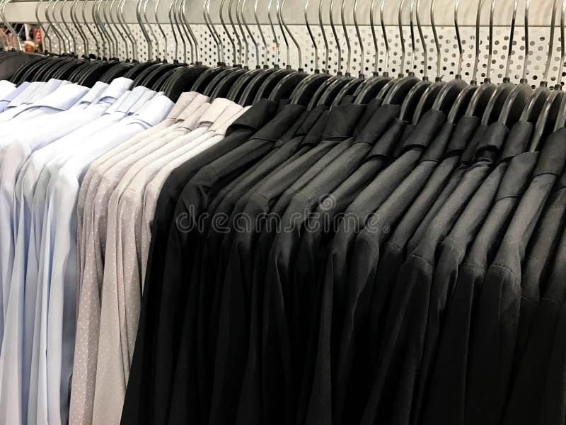 Slösa, gråna med den vita pricken och svärta skjortan på hängare i shopping royaltyfria bilder