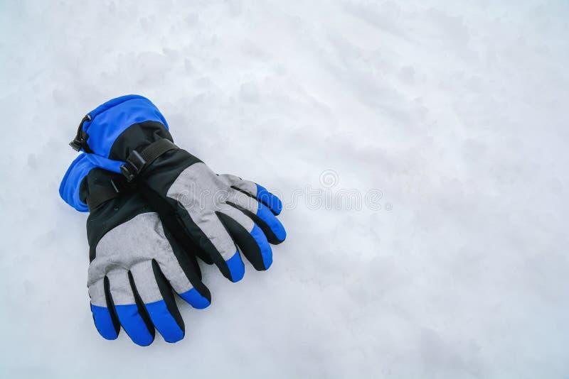 Slösa och gråna moderna skidåkninghandskar på vit snö för berget royaltyfri foto