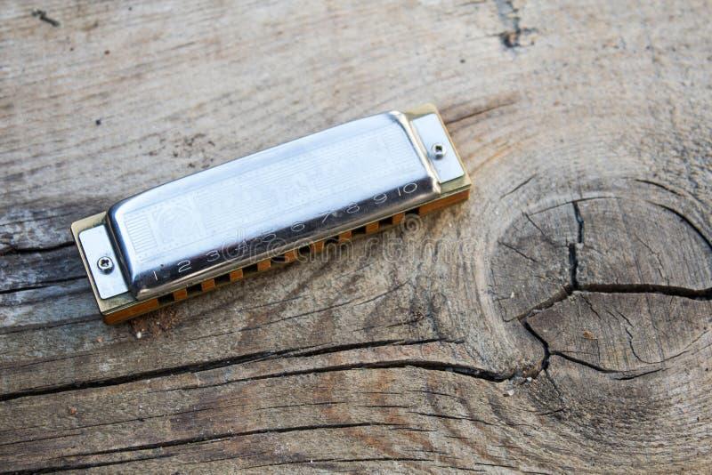 Slösar munspelmusikinstrumentet på en gammal wood bakgrund royaltyfri bild