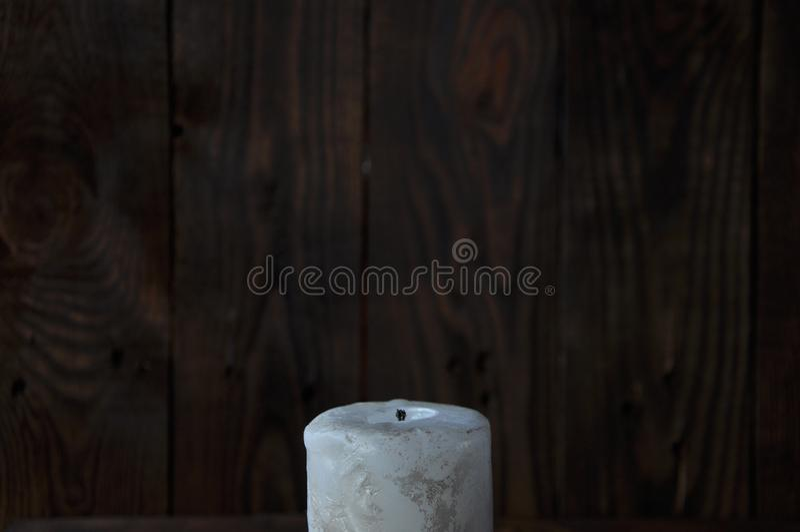 Sl?ckt stor vit stearinljus i m?rkret P? en tr?bakgrund arkivfoton
