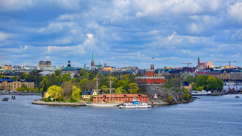 A SL public transport DJURGARDEN 9 ferry passes along islet Kastellholmen in front of small brick citadel Kastellet and vintage. STOCKHOLM, SWEDEN - May 03, 2019 royalty free stock photos