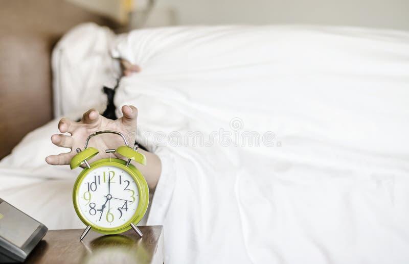 Slaap Aziatisch jong die mannetje door wekker wordt gestoord vroege ochtend stock foto