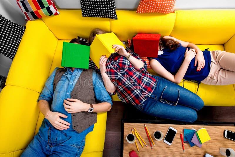 Slaap en vermoeide studenten op de laag stock foto