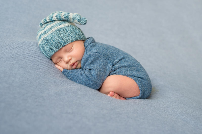 Slaap pasgeboren baby in blauwe jumpsuit en hoed stock foto