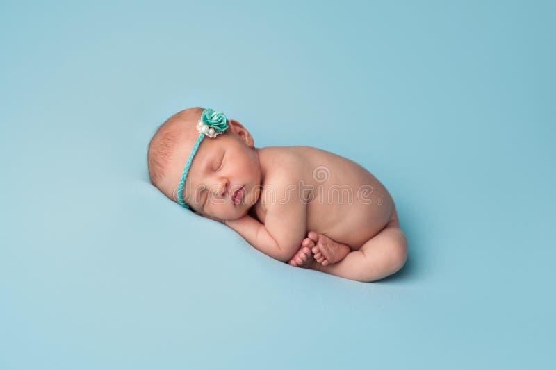 Slaap Pasgeboren Babymeisje met Blauwe Rose Headband stock afbeeldingen
