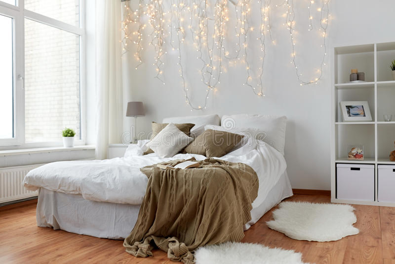 Slaapkamer met bed en Kerstmisslinger thuis royalty-vrije stock foto's