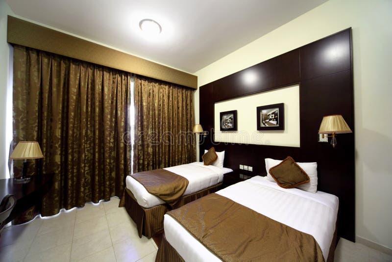 Slaapkamer met gesloten bruin gordijn en twee bedden stock fotografie