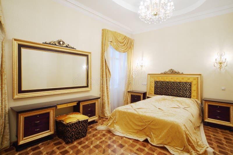 Slaapkamer met mooi bed bedlijsten en grote spiegel stock