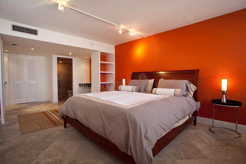 Slaapkamer met oranje muur stock afbeelding