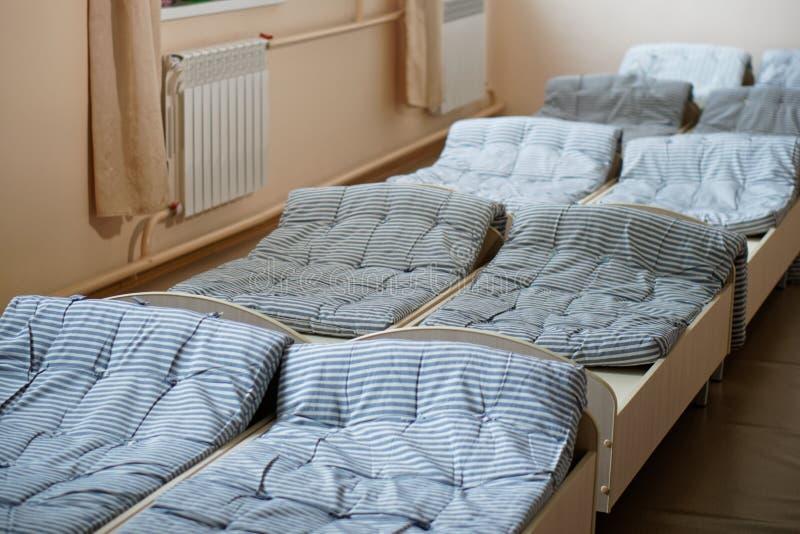 Slaapkamer van het verkennen van pioniers in het kamp van de de zomerkinderen Heel wat bedden en ascetisch binnenland royalty-vrije stock afbeeldingen