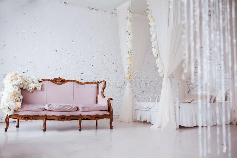 Slaapkamer in zachte lichte kleuren Groot comfortabel elegant tweepersoonsbed in het witte binnenland van de baksteenzolder royalty-vrije stock foto
