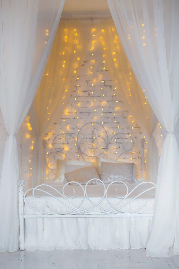 Slaapkamer in zachte lichte kleuren Groot comfortabel tweepersoonsbed in elegant klassiek binnenland royalty-vrije stock afbeeldingen