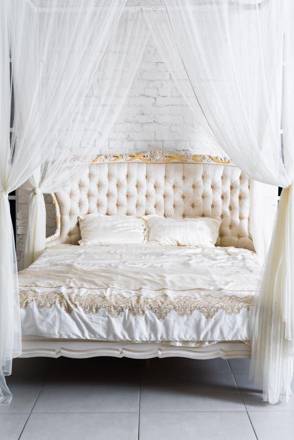 Slaapkamer in zachte lichte kleuren Groot comfortabel vier affiche tweepersoonsbed in elegante klassieke slaapkamer Luxewit met g stock afbeeldingen