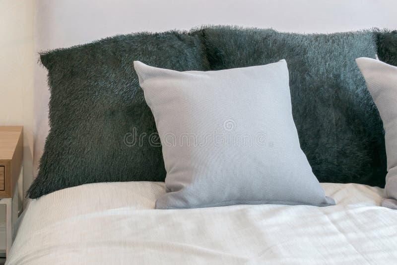 Slaapkamerbinnenland met grijze hoofdkussens op wit bed stock foto