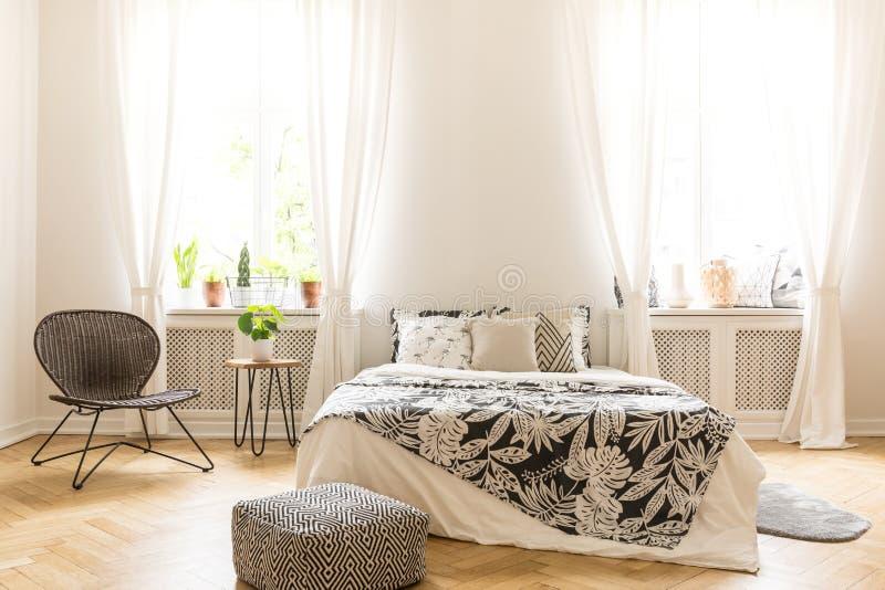 Slaapkamerbinnenland op z'n gemak met een beddegoed van het bladmotief op een bed, een rotanstoel en een zwart-witte poef die zic stock afbeelding