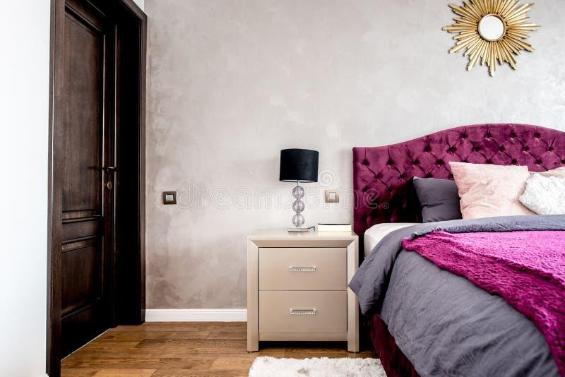 Slaapkamerdetails, hardhoutvloeren, comfortabel en modern meubilair en koningsgroottebed royalty-vrije stock afbeelding