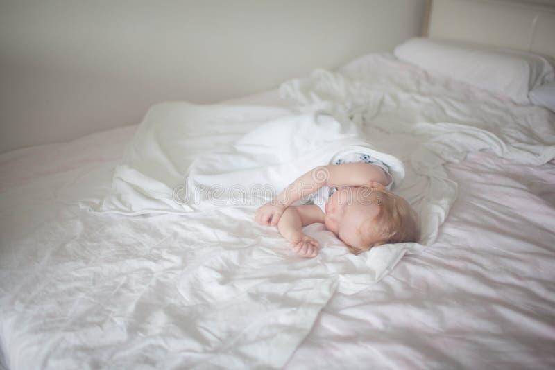 Slaapkind in een tweepersoonsbed stock afbeeldingen