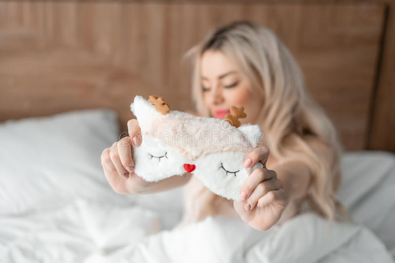 Slaapmasker in de voorgrond De jonge vrouw zit op comfortabel bed en greep in handenmasker voor slaap Ochtend in Hotel royalty-vrije stock afbeeldingen