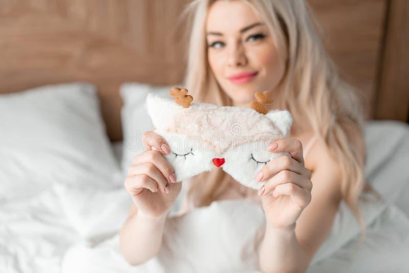 Slaapmasker in de voorgrond De jonge vrouw zit op comfortabel bed en greep in handenmasker voor slaap Ochtend in Hotel stock afbeelding