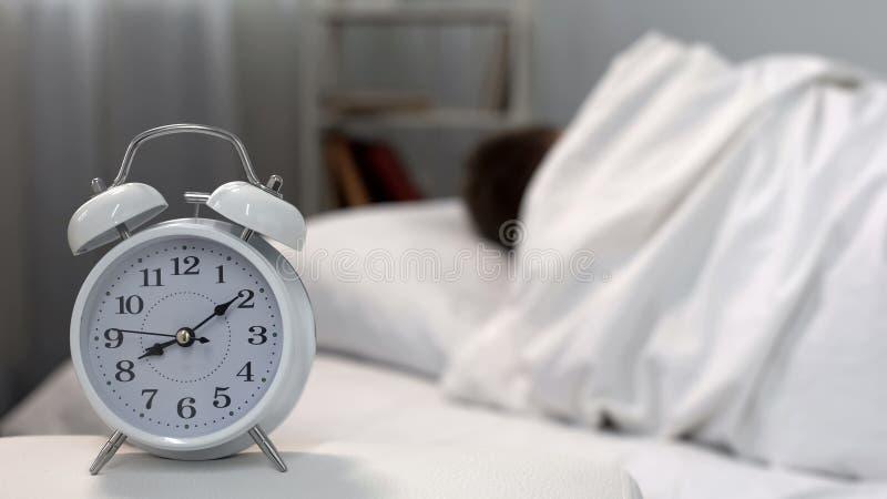 Slaapmens die bedklok in ochtend, tijdbeheer, zelf-discipline negeren stock afbeeldingen