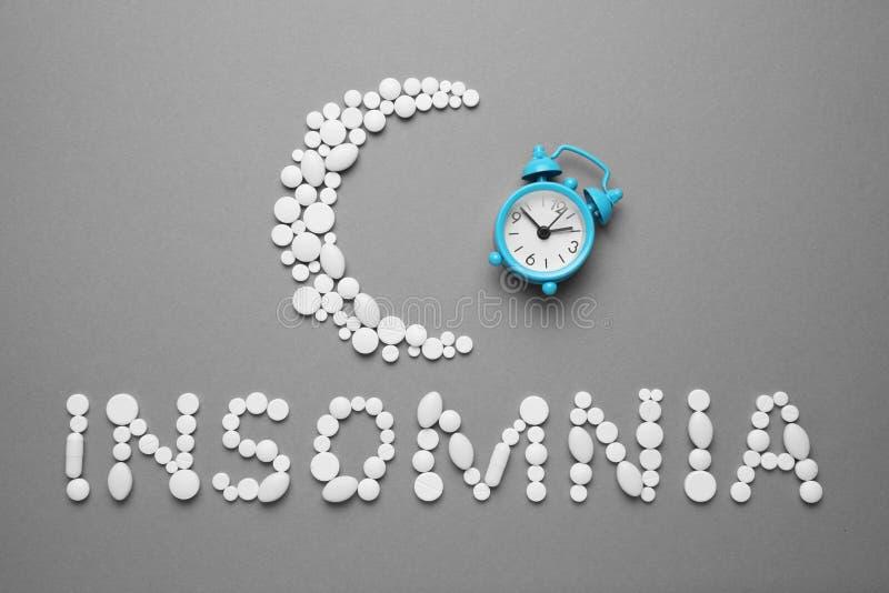 Slaappillen en een wekker, slapeloosheidsconcept Medicijnen voor moeheid en slaapproblemen royalty-vrije stock foto's