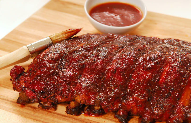 Slab of BBQ spare ribs. Slab of freshly grilled BBQ spare ribs with dipping sauce royalty free stock photography