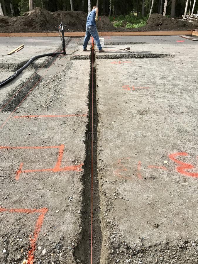 Slab on grade foundation preparation. Plumbing line trenches under slab on grade concrete foundation royalty free stock images