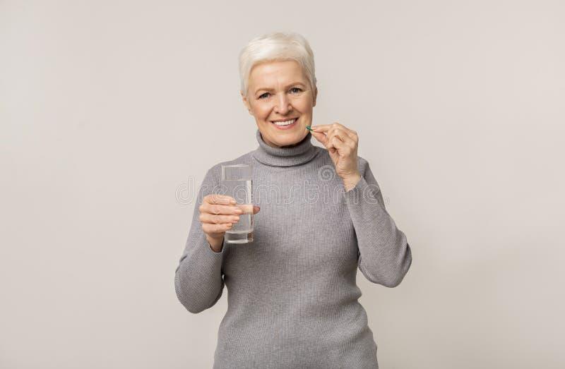 Slachende oudere vrouw die pillen neemt en glas water vasthoudt royalty-vrije stock fotografie